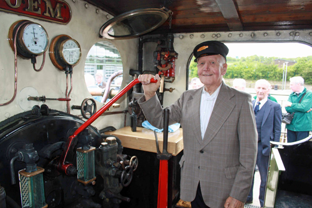 Retired driver Albert Hawman with his hand on the regulator again, whilst one time fireman Brian Swales looks on.