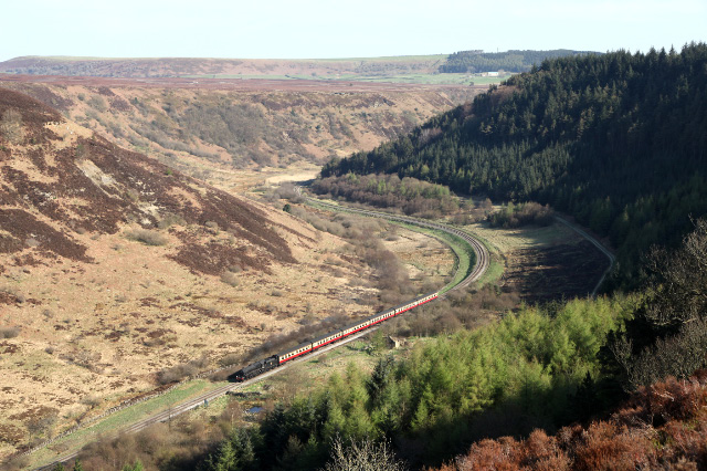 Perhaps the most spectacular and rarely seen view of any preserved railway in Britain shows Class 5 4-6-0 No 44871, with the matching blood and custard set of coaches, climbing past Carter's House in the heart of the twisting Newtondale Gorge and perhaps this view was the driving reason why Tom Salmon, founder of the NYMR, was so passionate about saving the Grosmont to Pickering line - Maurice Burns