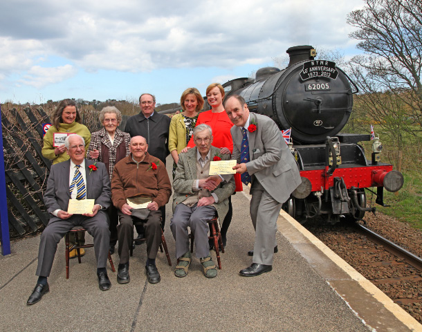 With the cooperation of Network Rail, the NYMR 40th Anniversary train makes a special stop to greet the three remaining founders of the NYMR. Here watched by their families are Michael Pitts (left), Charlie Hart (centre) whilst NYMR Trust Chairman Murray Brown presents a plaque to Tom Salmon whose idea and forward vision it was to save the Pickering line - Maurice Burns