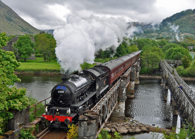Crossing the River Lochy. On the left is the ruin of Inverlochy Castle, the exhaust obscures the view up Glen Nevis of the Mamores, and on the extreme right the support coach can be glimpsed in the Fort William yard - Colin Smith