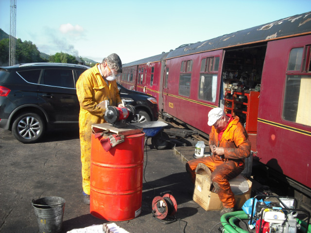 Nigel Hall and Steve Gibson cleaning the washout plugs and doors. The high pressure pump for washing out can be seen at bottom RHS. Rumors that Florence is driving a steam powered car are not true; the smoke comes from the chimney of Bert Hitchens's black 5 in the distance  - John Midcalf