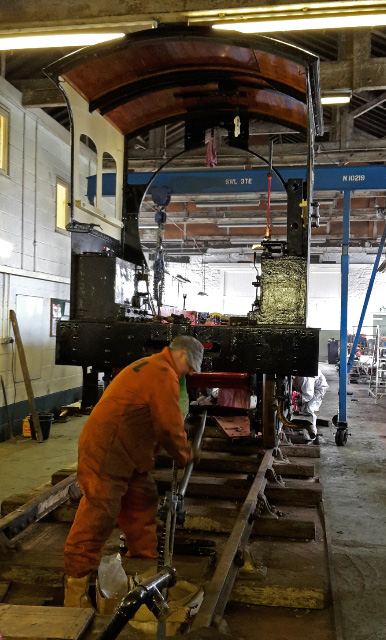 Trevor Wilford on the pullift and Andrew Jacques on pinch bar moving the locomotive back out of the way of the hoist after attaching the cab - Nigel Hall